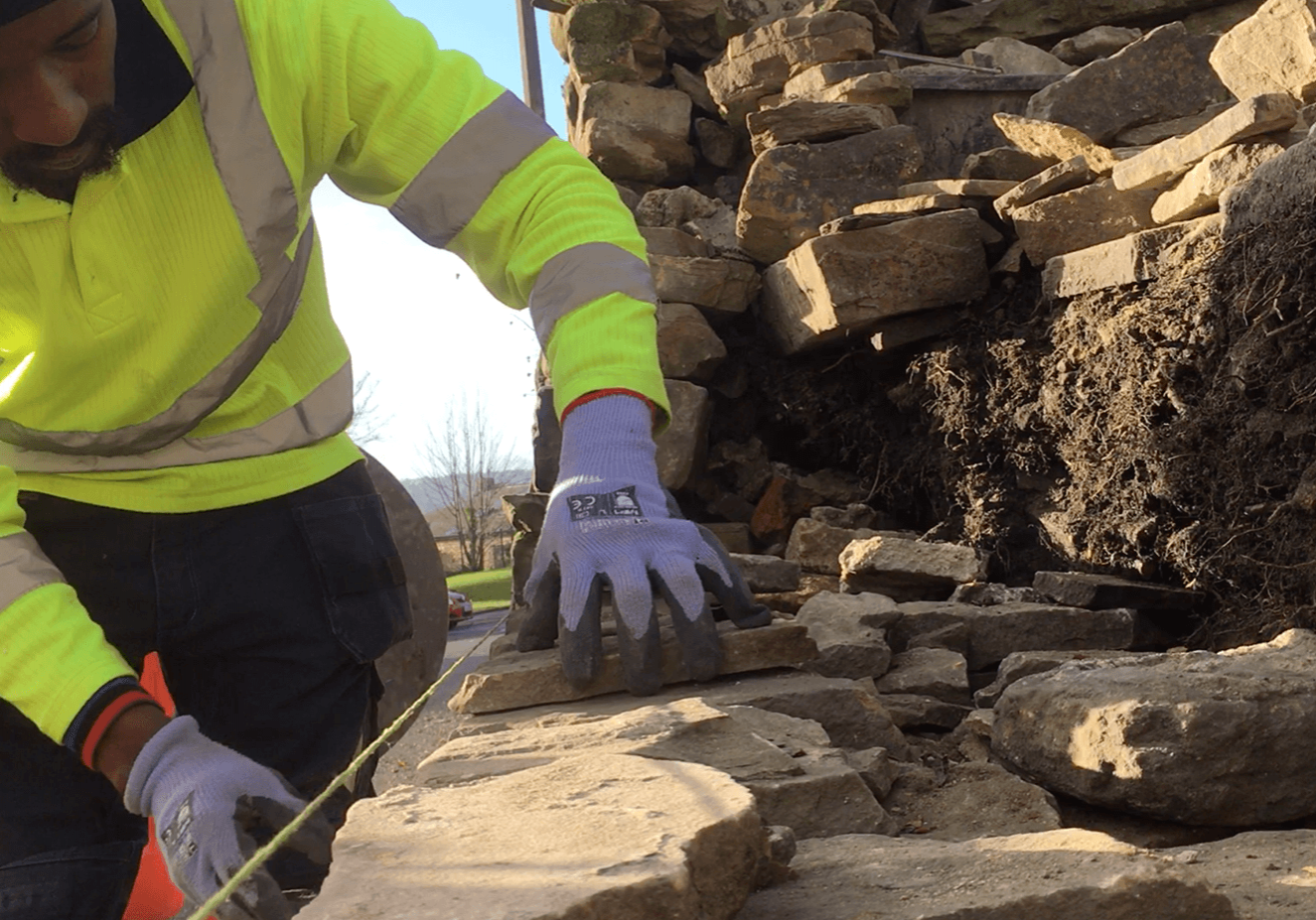 Trainee building dry stone wall section